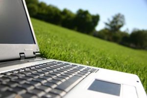 Silver laptop on green grass outside in the sunshine